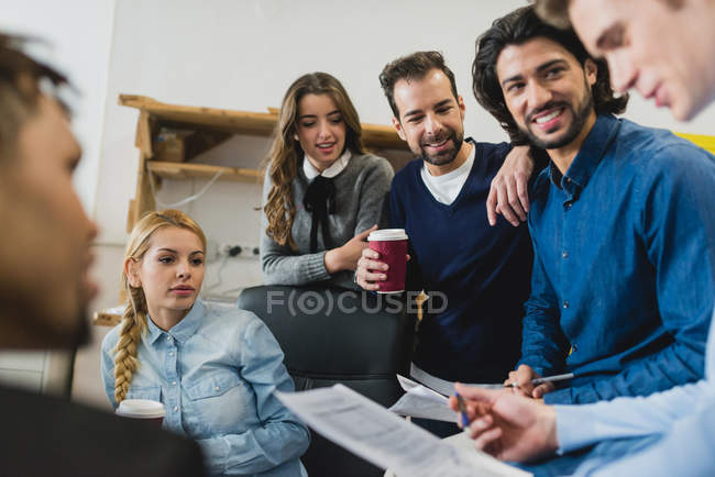 Portrait of smiling office team members listening to colleagues report at daily meeting — Stock Photo