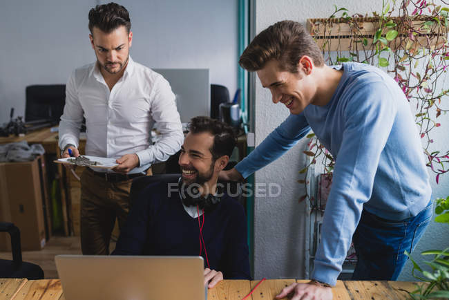 Portrait of entrepreneurs looking at colleagues laptop screen at workplace — Stock Photo
