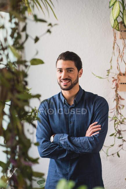 Porträt eines Mannes, der mit gekreuzten Händen am Fenster steht und in die Kamera blickt — Stockfoto