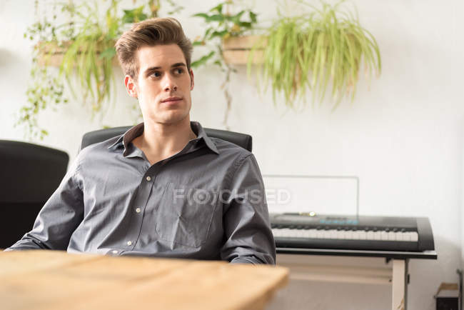 Confident businessman sitting at workplace in office and looking aside — Stock Photo