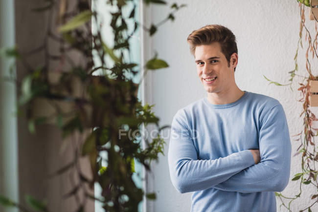 Portrait of smiling employee posing near window and looking at camera — Stock Photo