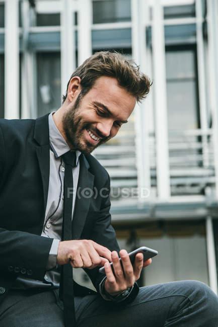 Empresário elegante usando um Smarthpone em uma área financeira — Fotografia de Stock