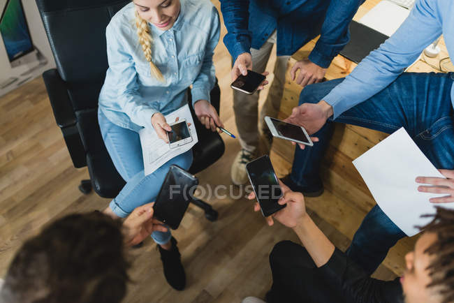High angle view of multi-ethnic business people using smartphones at meeting in office — Stock Photo