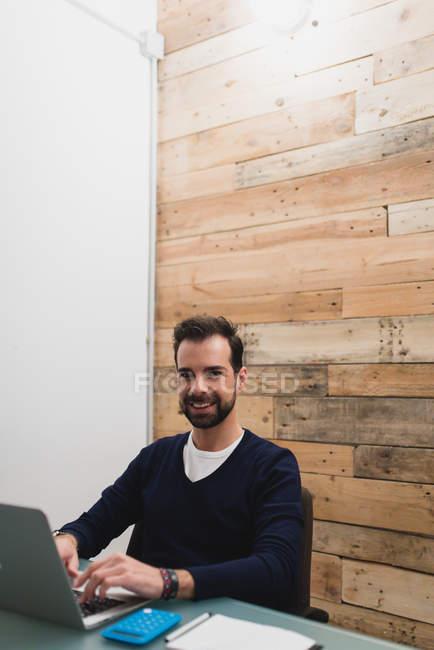 Ritratto di impiegato sorridente che digita sul computer portatile e guarda la macchina fotografica . — Foto stock