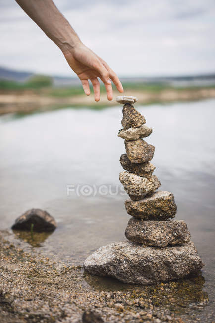 Crop hand stretching to stone tower — Stock Photo