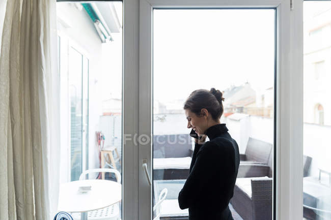 Вид сбоку на женщину, стоящую у окна и говорящую по телефону — стоковое фото