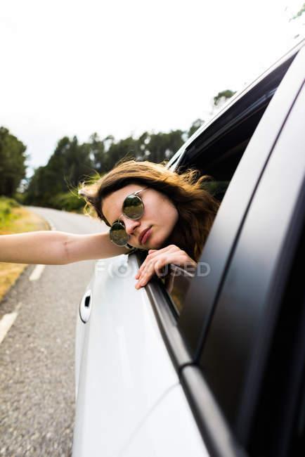 Стильна дівчина дивиться з вікна автомобіля — стокове фото