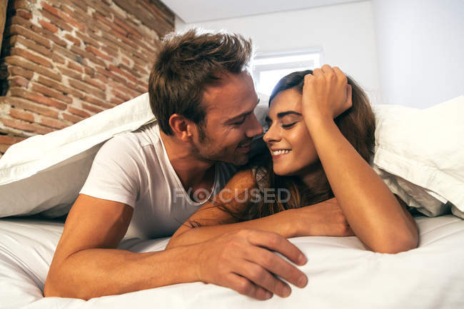 Couple flirter dans son lit — Photo de stock