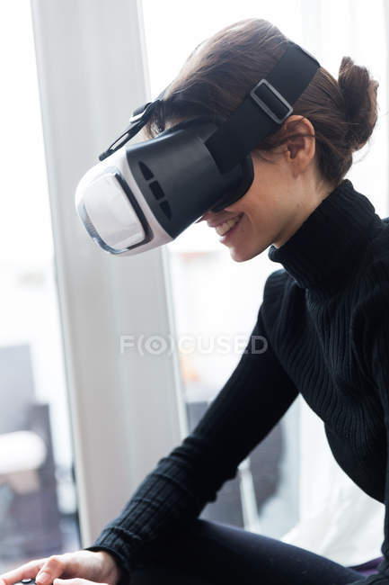 Side view of brunette girl wearing virtual reality glasses and playing video game — Stock Photo