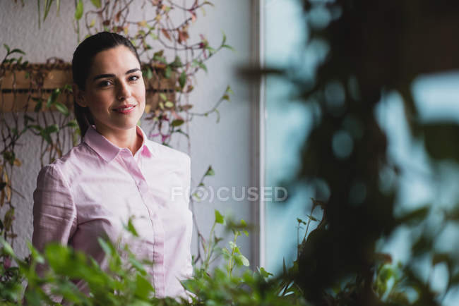 Portrait of businesswoman standing near window in office and looking at camera — Stock Photo