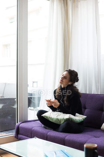 Brunette girl with earphones and smartphone sitting on coach with legs crossed and enjoying music with eyes closed — Stock Photo