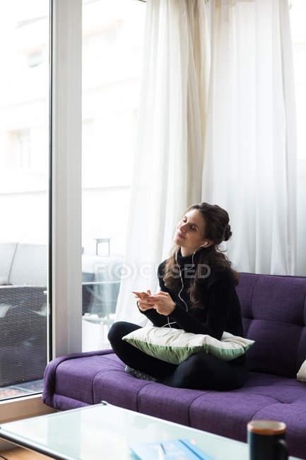 Брюнетка девушка с наушники и смартфон, сидя на тренер с ногами перешли и наслаждаться музыкой с глазами закрыт — стоковое фото