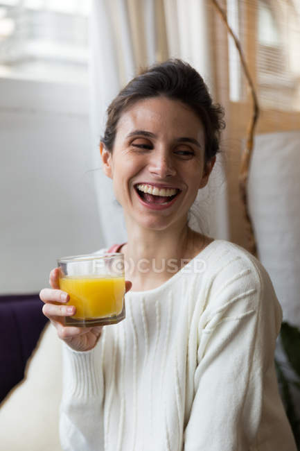 Сміючись Жінка тримає склянку апельсинового соку і дивиться в бік — стокове фото