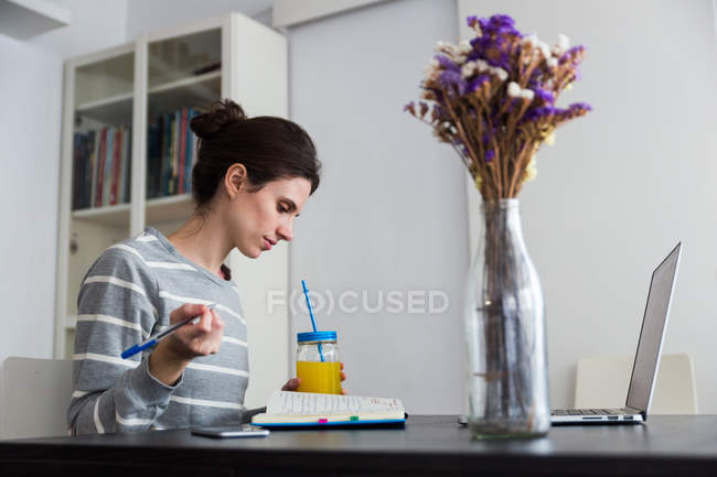 Side view of brunette woman with jar of orange juice sitting at table with laptop and looking down at notebook — Stock Photo