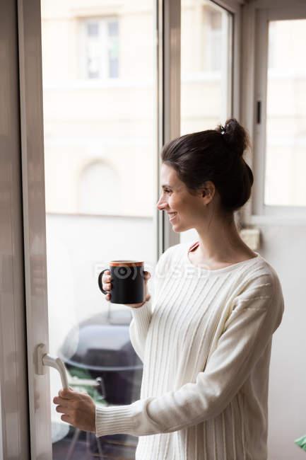 Vista lateral da menina morena com copo nas mãos janela de abertura em casa — Fotografia de Stock