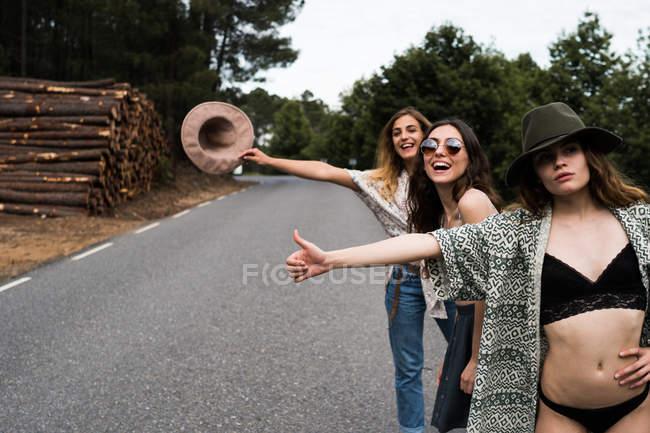 Женщины, автостопом на дороге — стоковое фото