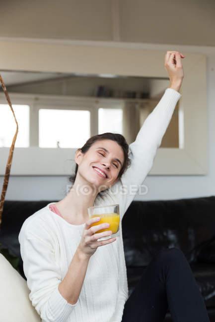 Портрет брюнетка Жінка тримає склянку апельсинового соку і розтягування очі закриті — стокове фото
