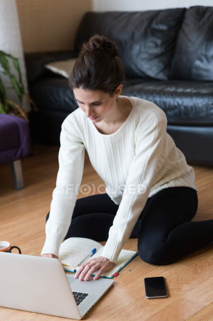 Woman sitting on floor with lying notebook and using laptop. — Stock Photo