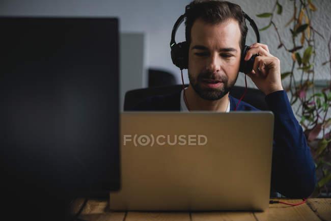 Retrato do homem sentado à mesa, ajustando os fones de ouvido e olhando para baixo para portátil — Fotografia de Stock