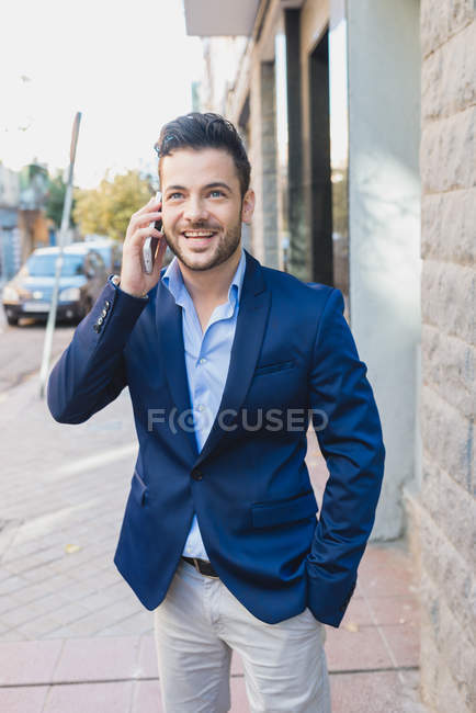 Portrait of businessman standing outside office and having phone conversation. — Photo de stock