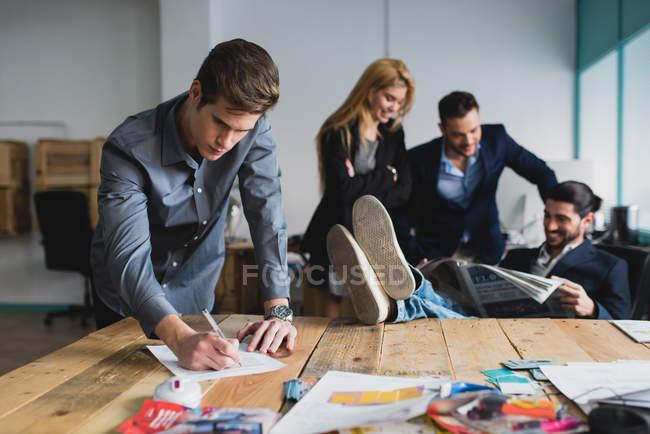 Retrato del hombre firmando papeles sobre los trabajadores de oficina en segundo plano - foto de stock
