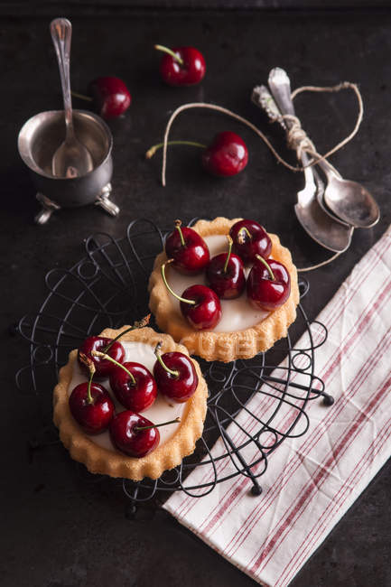 Tartlets filled with cream and cherries — Stock Photo