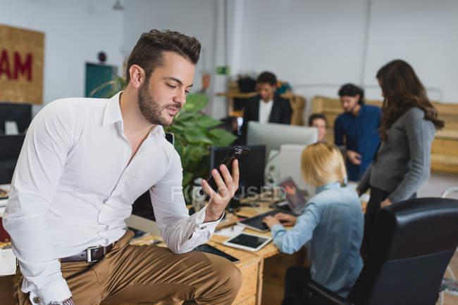 Портрет человека, сидящего на столе и пользующегося телефоном над офисными работниками на заднем плане — стоковое фото