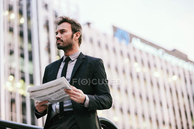 Businessman Holding a Newspaper in a Finance Area — Stock Photo