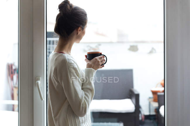 Side view of girl in white sweater posing near window with mug in hands — Stock Photo