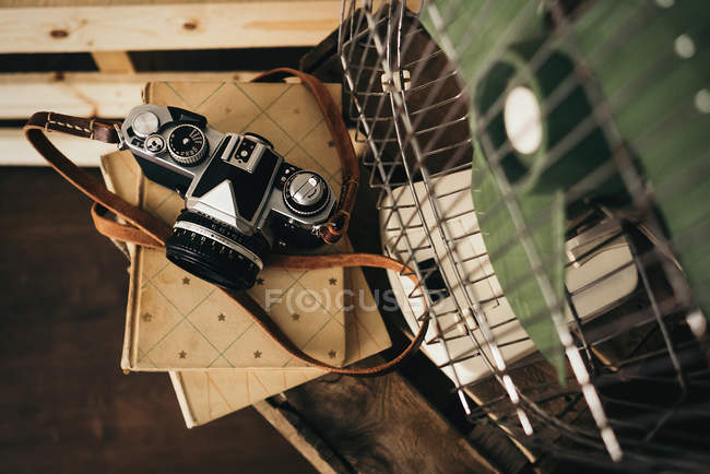 From above shot of retro camera on notepad and vintage fan — Stock Photo
