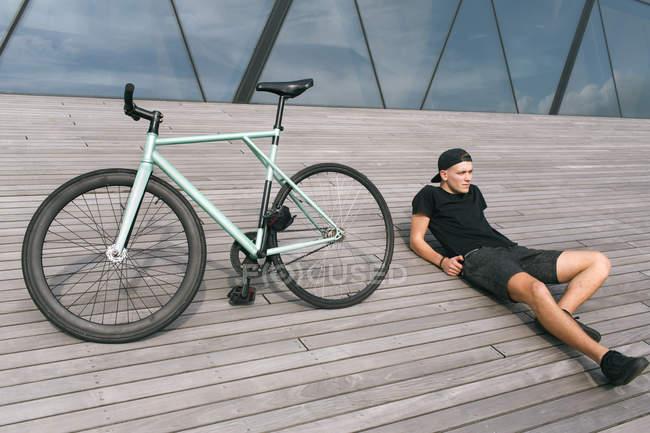Человек, сидящий рядом со своим велосипедом — стоковое фото