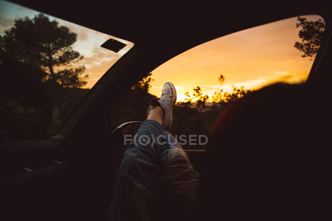 Person lying in car and holding legs out of window. — Stock Photo