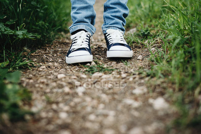Legs of person wearing gumshoes standing on path in grass — Stock Photo