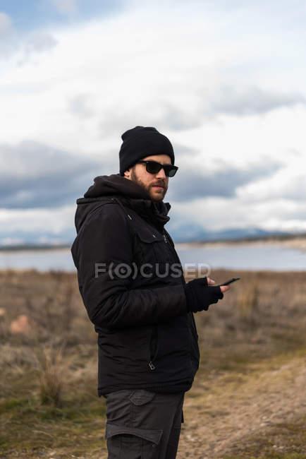 Stylish man in warm clothing using phone — Stock Photo