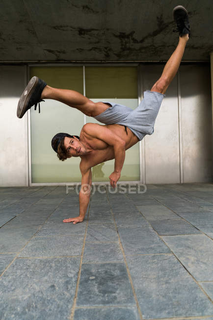 Shirtless man in handstand on street — Stock Photo