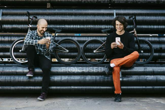 Masculino BMX pilotos em tubos com telefones — Fotografia de Stock