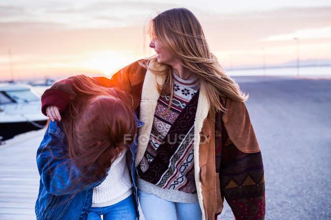 Couple de femmes s'amuser au coucher du soleil — Photo de stock