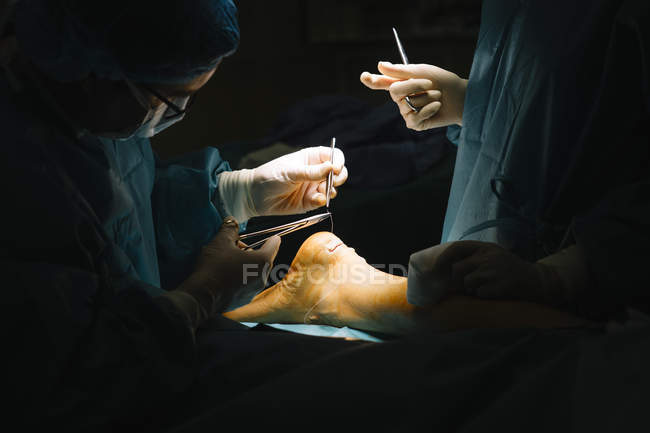 Surgeon sewing up Achilles tendon — Stock Photo