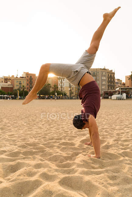 Mann im Handstand am Strand — Stockfoto