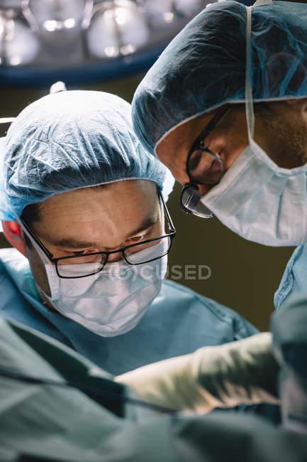Cirurgiões em máscaras operando — Fotografia de Stock