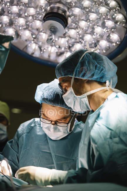 Cirurgiões de operação sob a lâmpada de processamento — Fotografia de Stock