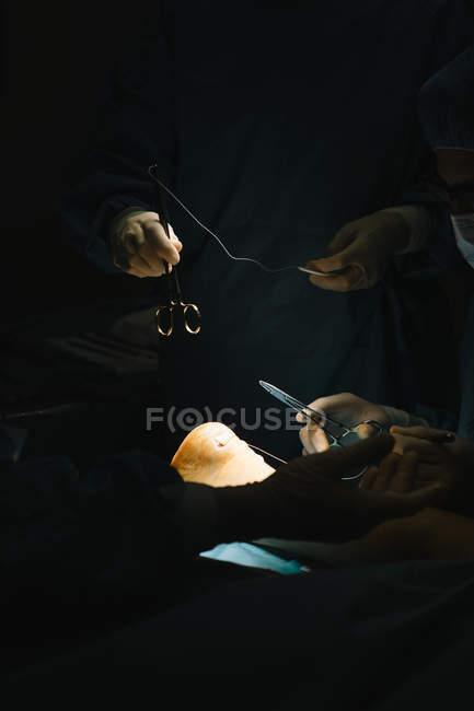 Mains avec outils chirurgicaux sur la cheville — Photo de stock