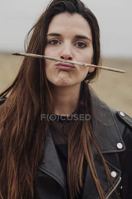 Donna che tiene un ramo con le labbra — Foto stock
