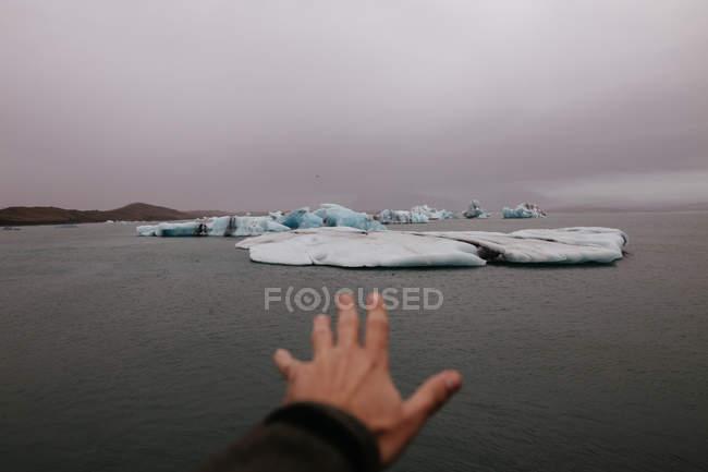 Рука культур вытянутыми на ледник — стоковое фото