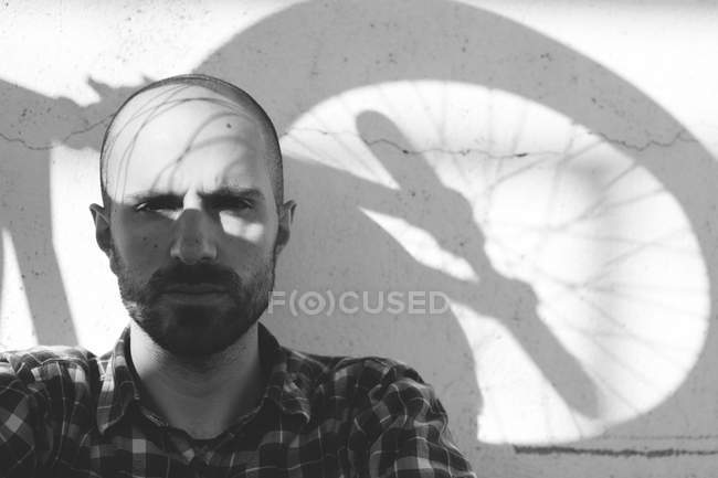 Man with bike wheel shadow on face — Stock Photo