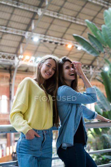 Deux filles souriantes à main courante — Photo de stock
