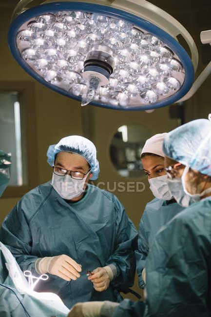 Команда хирургов смотрит на пациента — стоковое фото