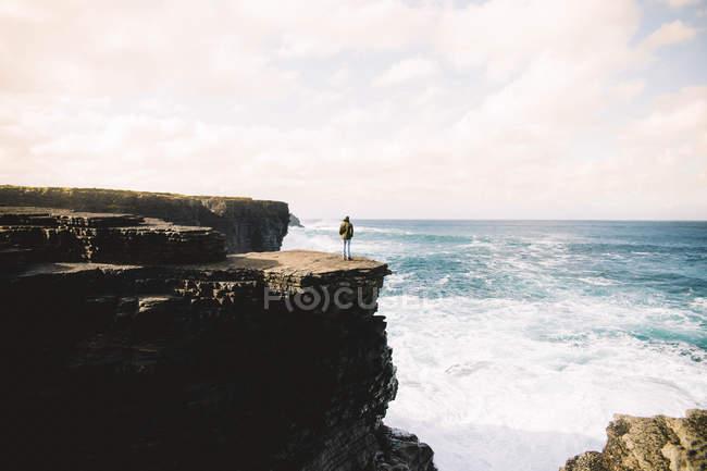 Vista traseira da pessoa em pé em cima da parede de montanha e no mar procurando água — Fotografia de Stock