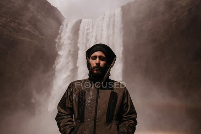Молодой человек в халате на водопад — стоковое фото
