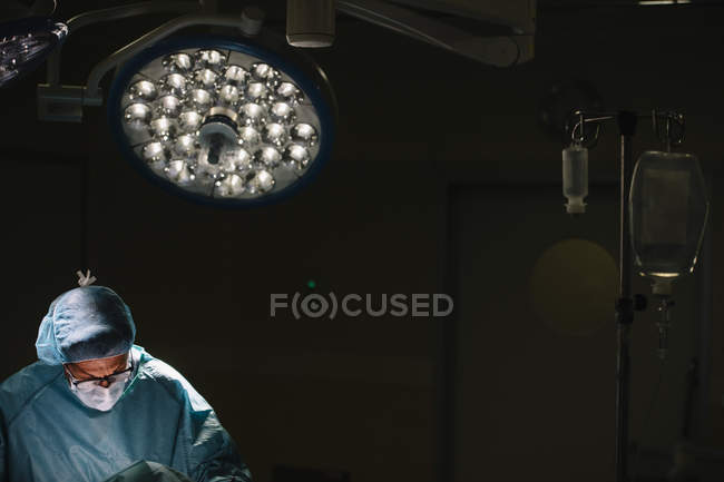 Surgeon in mask operating under lamp — Stock Photo